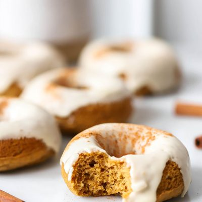 vegan baked pumpkin donuts with maple frosting on white marble