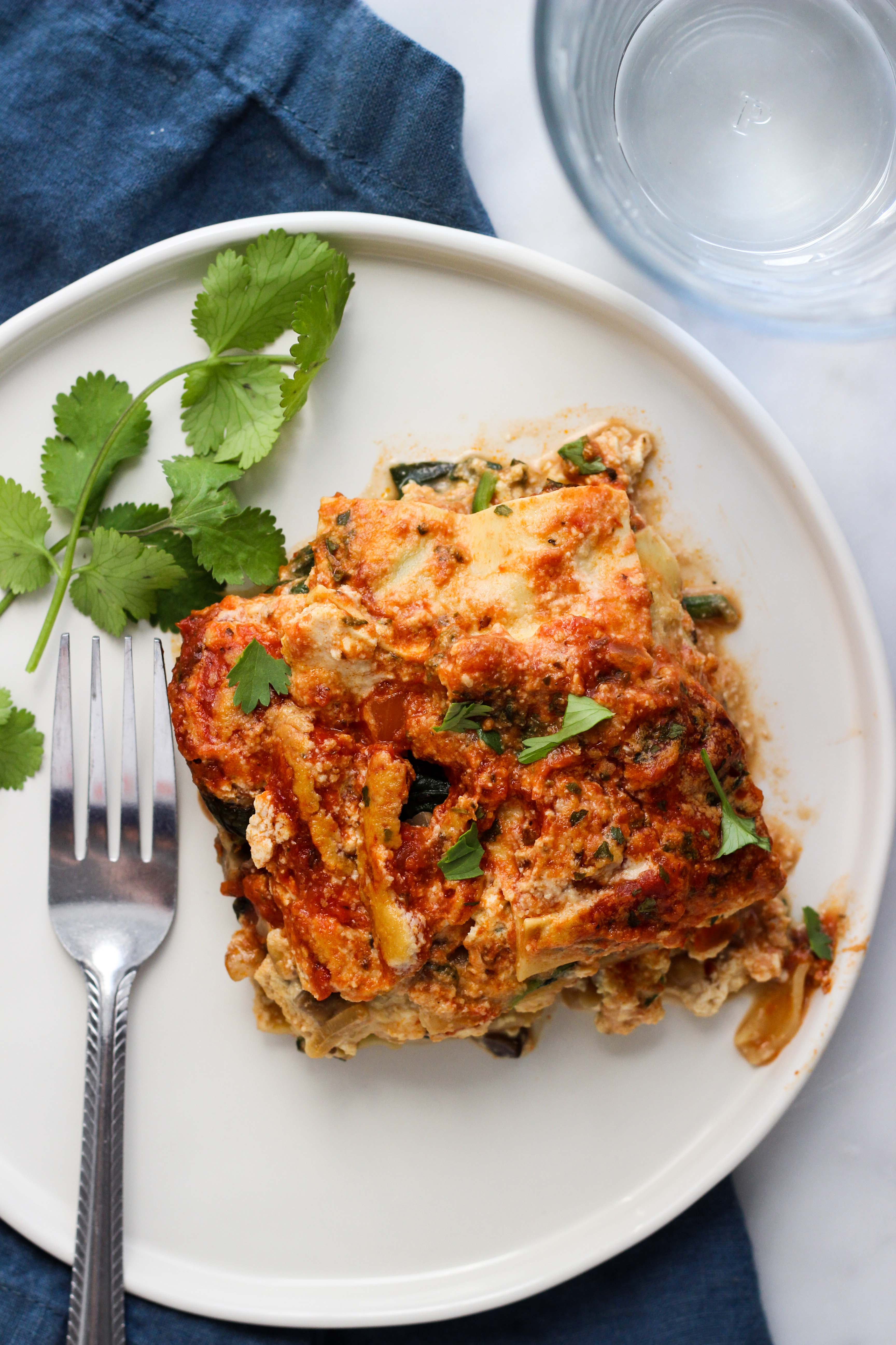 Vegan Spinach and Mushroom Lasagna on white plate with fork