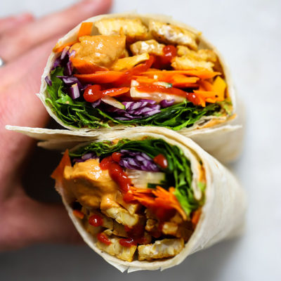 Tempeh wrap with peanut sauce held up with hand