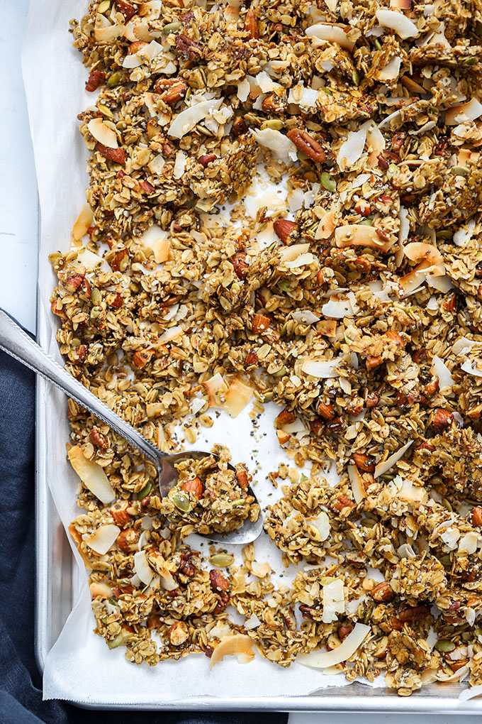 healthy super seedy granola on sheet pan with spoon