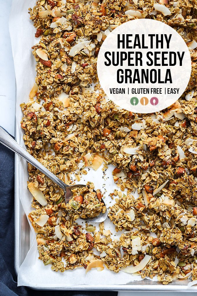 healthy super seedy granola on sheet pan with spoon and text