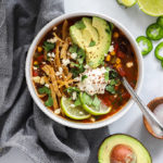 Tortilla soup topped with avocado, lime, and sour cream