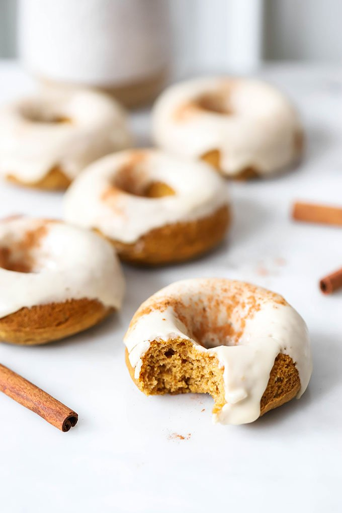 vegan baked pumpkin donuts with maple frosting on white marble background