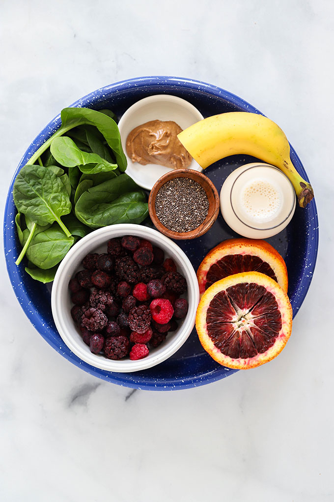 blood orange smoothie ingredients on a blue tray