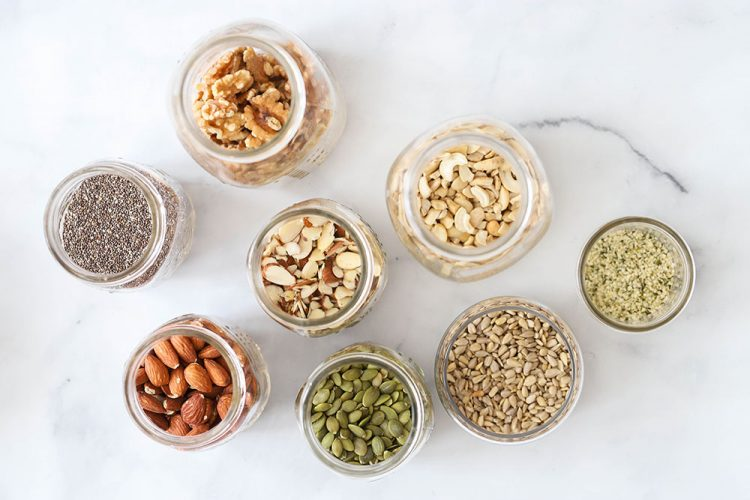 nuts and seeds in jars on marble background