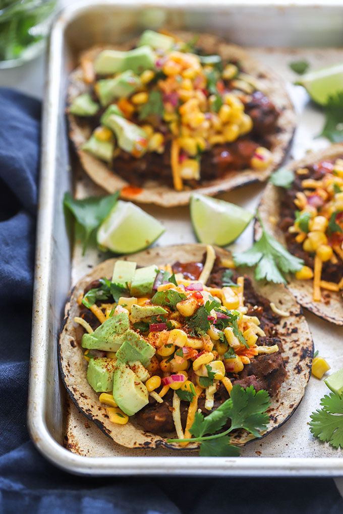 close up photo easy vegan black bean tostadas on baking sheet