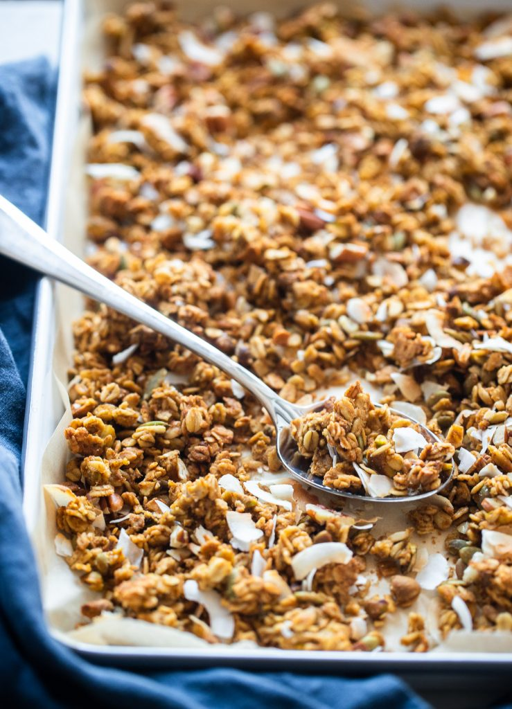 pumpkin spice granola on sheet pan with spoon